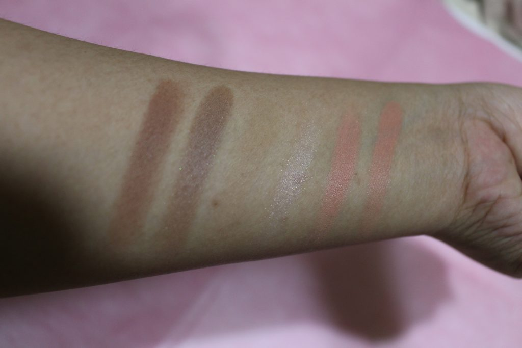 Left to Right: 1st shade on 1st row, a warm contour shade; 1st shade on 2nd row, a cool-toned contour shade; 2nd shade on 1st row, a bronzer shade; 2nd shade on 2nd row, a highlighter; 3rd shade on 2nd row, a pink blush; 3rd shade on 1st row, a coral blush with specks of glitter